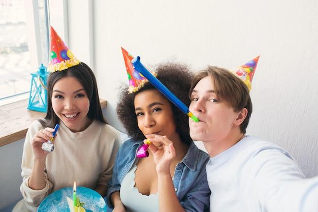 Guy prend un selfie avec ses deux amis. ils célèbrent l'anniversaire des filles afro-américaines. les gens portent des chapeaux d'anniversaire. les filles aussi ont des whisltes.