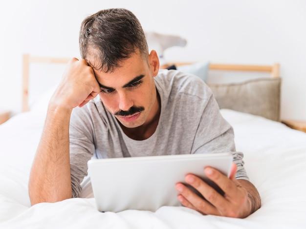 Guy s'ennuie en regardant un film sur son lit