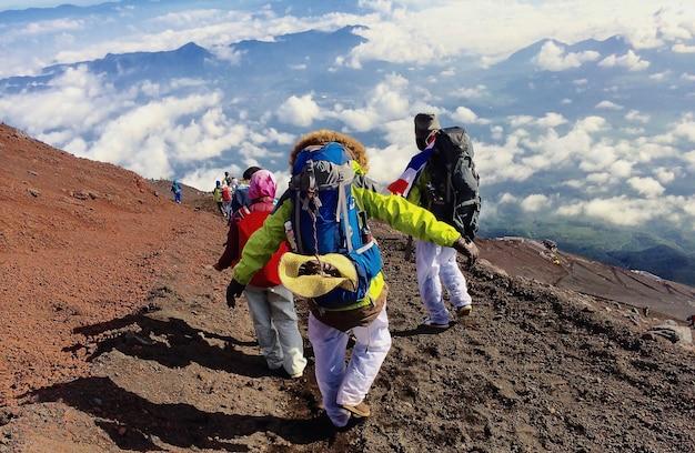 Guy avec un sac à dos de voyage sur le haut d'un rocher