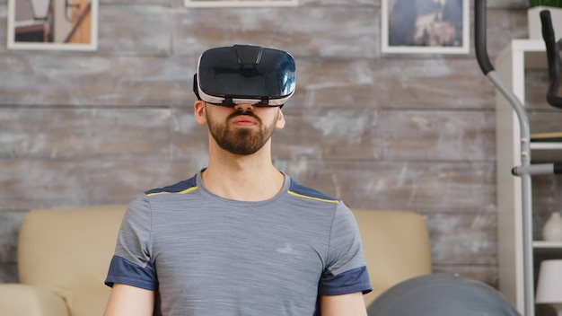 Guy se concentre sur la respiration en faisant du yoga avec un casque de réalité virtuelle.