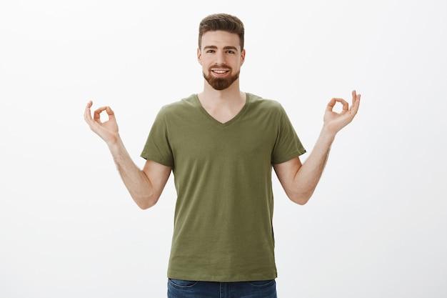 Guy se sentant calme et détendu, sans stress grâce à de nouvelles pilules, souriant largement et libéré se tenant la main en zen, geste de lotus souriant heureux de méditer et de pratiquer le yoga sur un mur blanc