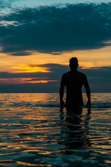Guy sortant de la plage au coucher du soleil.