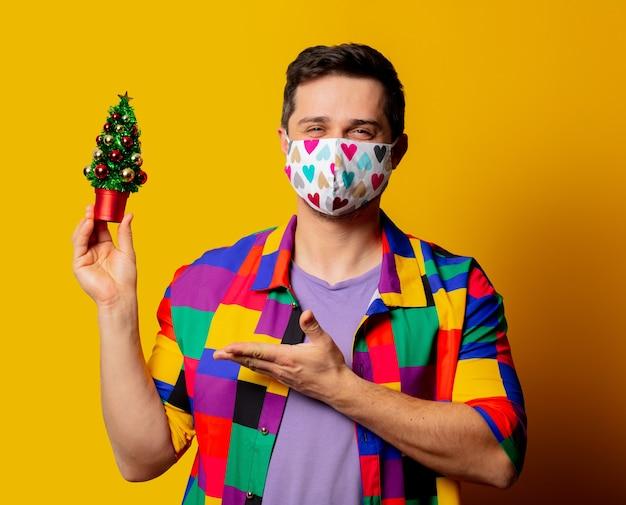 Guy de style en chemise des années 90 et masque facial avec arbre de noël