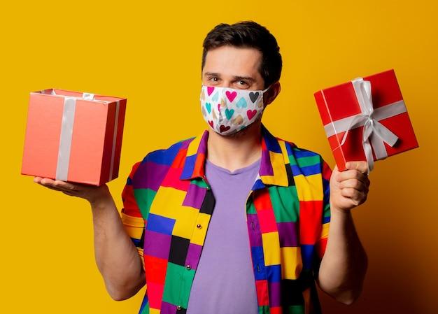 Guy de style en chemise des années 90 et masque facial avec boîte-cadeau