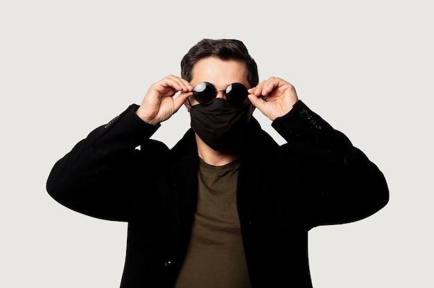 Guy de style en manteau noir, masque facial et lunettes de soleil