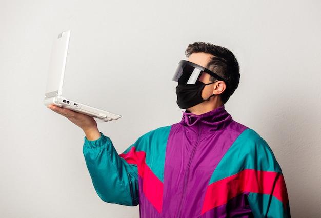 Guy de style en veste des années 90 et masque facial avec ordinateur portable