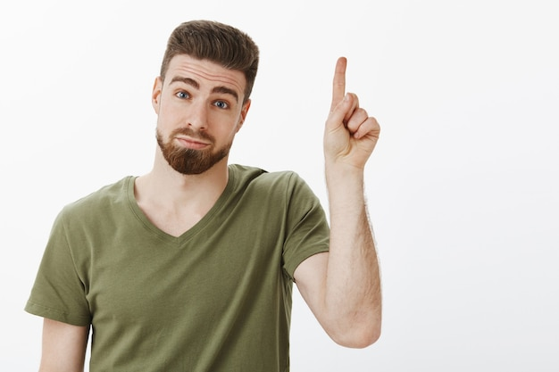 Guy a une suggestion en levant l'index ajouter une idée debout idiot et mignon avec une expression hésitante et timide faisant la tête inclinée et regardant avec un sourire mignon, pointant vers le haut sur un mur blanc