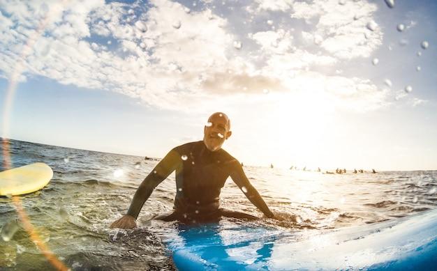 Guy surfeur se reposant sur une planche de surf au coucher du soleil à tenerife avec des personnes méconnaissables sur des planches de surf en arrière-plan - concept de voyage sportif avec une faible profondeur de champ avec des gouttes sur l'objectif comme composition