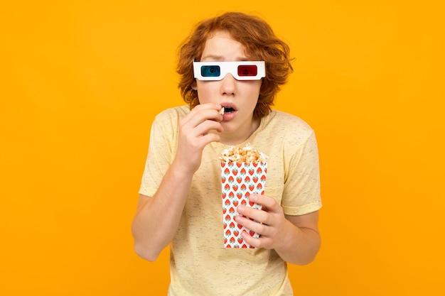 Guy Surpris Dans Un T-shirt Avec Du Pop-corn En Regardant Un Film Avec Des Lunettes 3d Sur Fond Jaune Avec Espace De Copie. Photo Premium