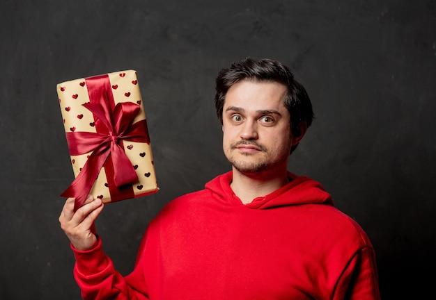 Guy en sweat-shirt rouge coffret cadeau sur mur sombre