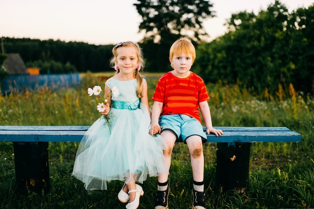 Guy de taches de rousseur avec une peau pâle et des genoux sales assis avec une petite fille gentille en robe bleue sur un banc en soirée d'été à la nature.