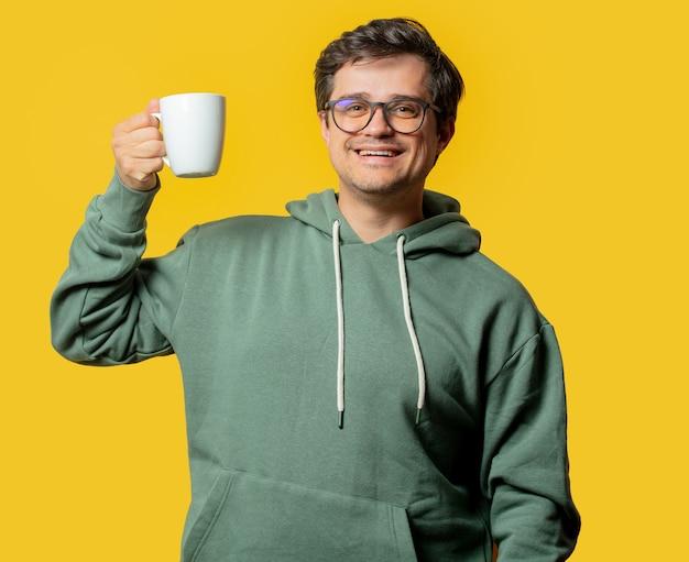 Guy avec tasse de café et sweat à capuche vert sur jaune
