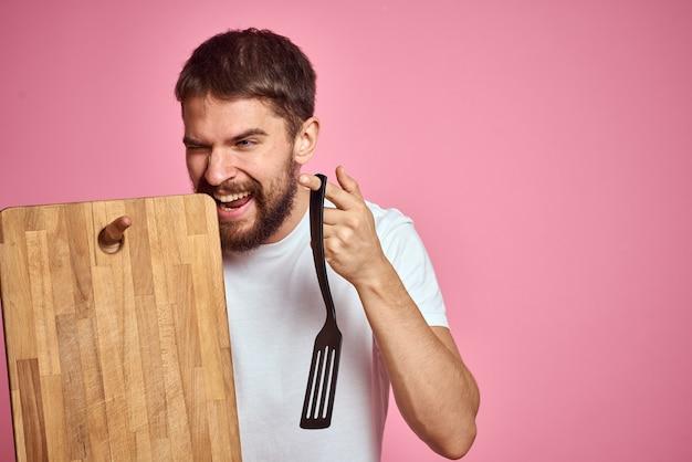 Guy tenant la planche de cuisine et la spatule à la main sur la vue recadrée de fond rose. photo de haute qualité