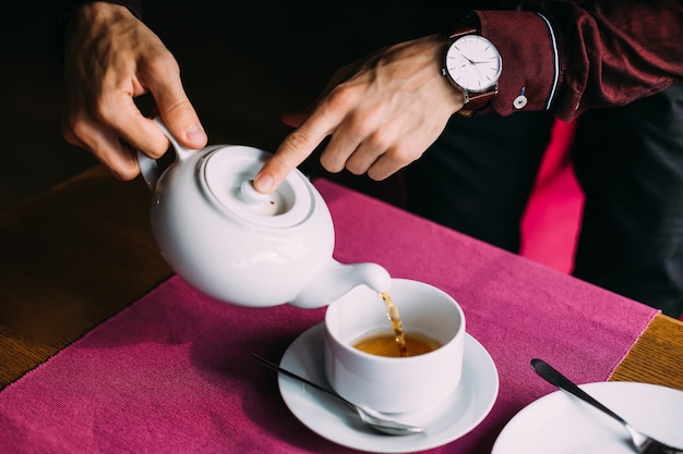 Guy tient la bouilloire et verse du thé chaud dans la tasse