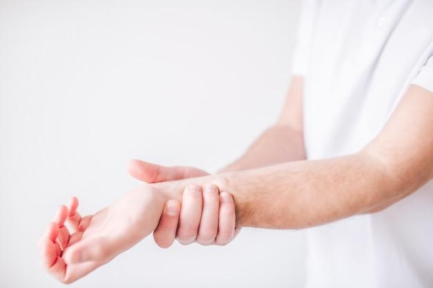Guy tient sa main par le poignet à cause de la douleur et de la douleur