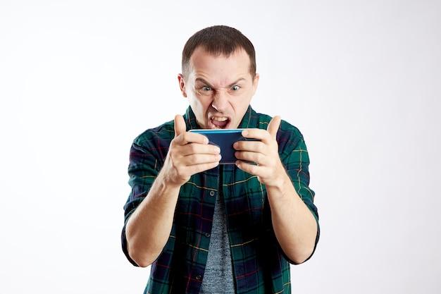 Guy tient le téléphone dans ses mains et le montre du doigt. un homme joue sur son téléphone et regarde des vidéos, des réseaux sociaux