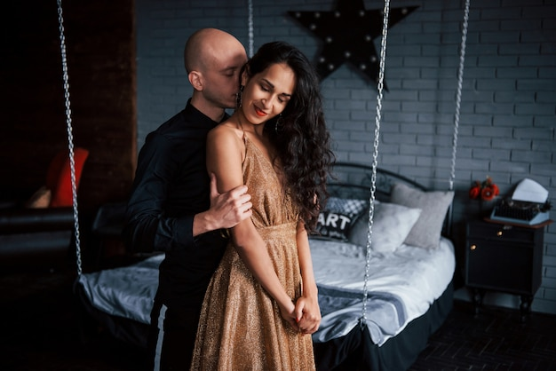 Guy touche la fille par derrière. couple en vêtements classiques se tient devant le beau lit décoré de luxe