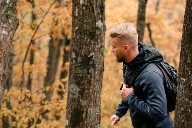 Guy touriste se promène dans une forêt d'automne brumeuse