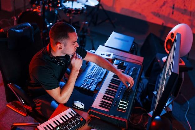 Guy a un travail de projet et de mixage de musique à l'intérieur du studio.