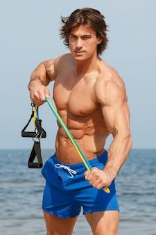 Guy travaillant avec élastique sur la plage
