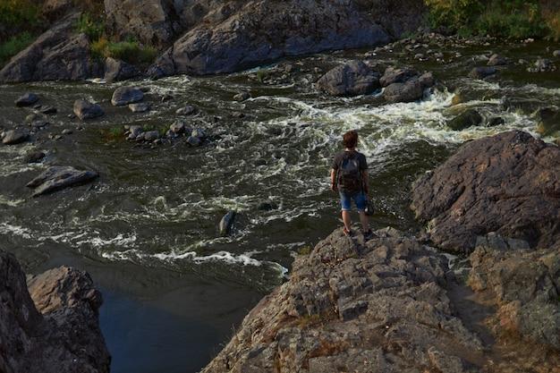 Guy traveler se tient sur les rochers surplombant la rivière de montagne et regarde au loin en haute qua...