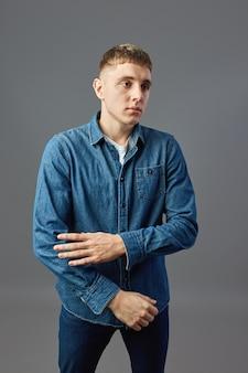 Guy vêtu d'un t-shirt blanc, d'un jean et d'une chemise en jean debout, les bras croisés en studio sur fond gris.