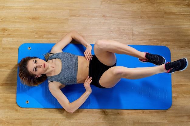 Gym abs la fille fait des exercices sur la presse abdominale.