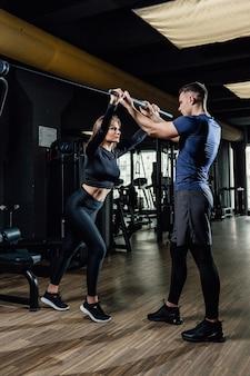 Gym entraîneur personnel homme avec barre de musculation entraînement femme en exercice de remise en forme