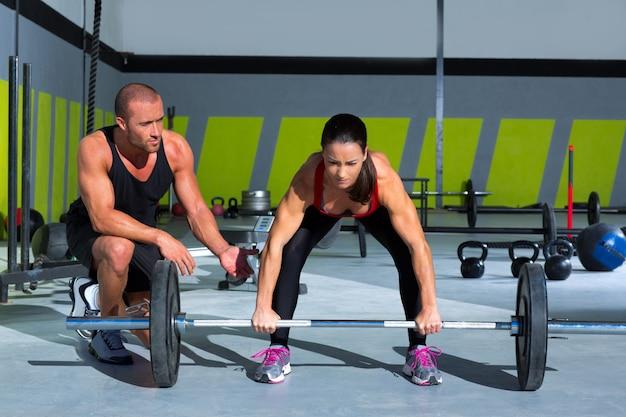 Gym entraîneur personnel homme avec haltérophilie femme
