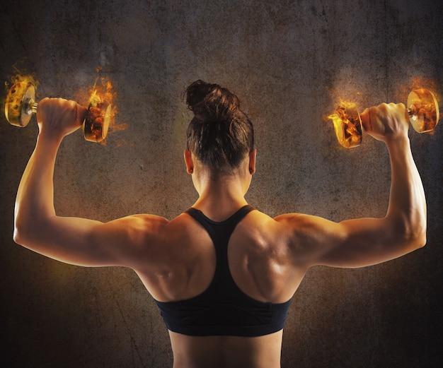 Gym femme train de retour avec des haltères enflammés