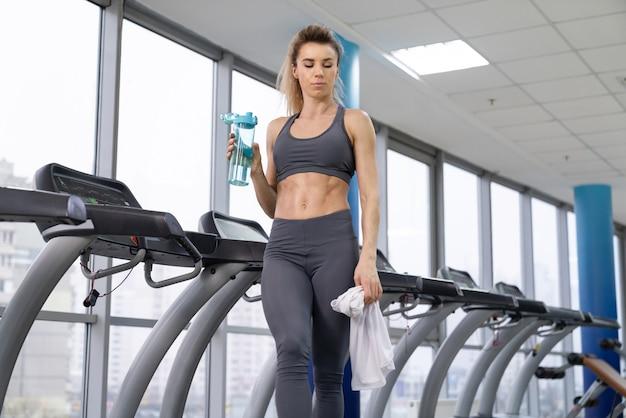 Gym femme travaillant sur l'eau potable debout par des machines de fitness