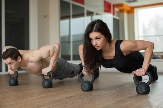 Gym homme et femme push-up force pushup avec kettlebells dans une séance d'entraînement de remise en forme