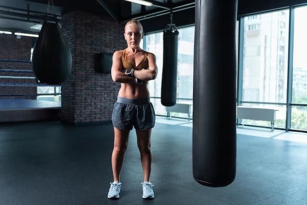 Gymnase moderne. femme musculaire aux cheveux blonds debout au milieu de la salle de sport moderne tout en s'entraînant dur