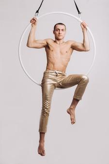 Gymnaste aérien mâle exécute l'élément acrobatique dans le ring