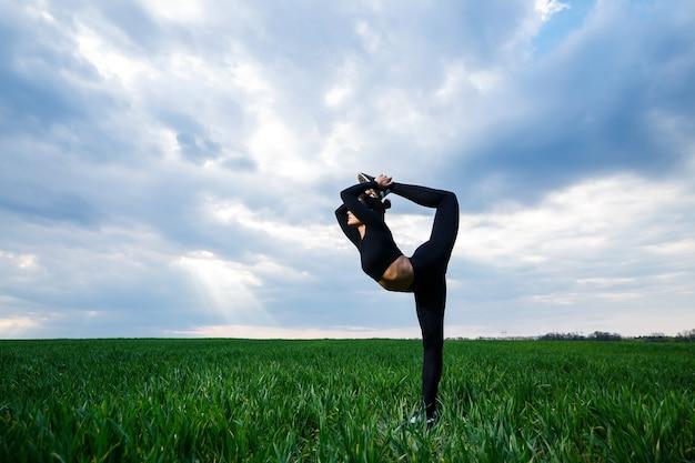 Gymnaste de belle fille sur l'herbe verte faire du yoga. une belle jeune femme sur une pelouse verte exécute des éléments acrobatiques. gymnaste flexible en noir fait le poirier en split