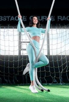 Gymnaste de belle fille s'échauffant dans la salle d'athlétisme