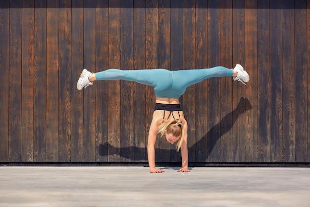 Gymnaste de belle jeune fille athlétique en tenue de sport, travaillant, élément de gymnastique, faisant le grand écart.