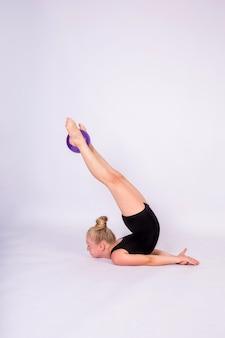 Une gymnaste blonde dans un maillot de bain noir se dresse sur ses épaules avec un ballon sur un mur blanc isolé avec un espace pour le texte