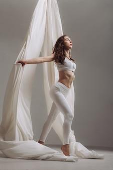 Gymnaste féminine posant avec des rubans de soie aérienne