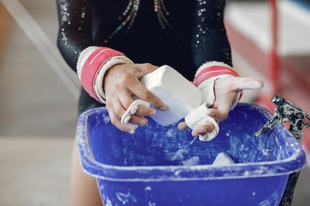 Gymnaste de fille dans les poignées de gymnastique étalant la craie de gym. enfant dans une école d'athlétisme.