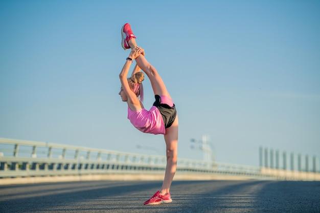 Gymnaste fille engagée à l'été dans la rue, sur fond de ciel bleu, ficelle, étirement, arabesque
