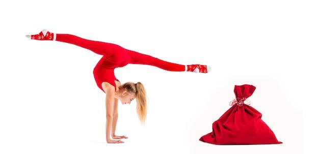 Gymnaste de fille mince en costume moulant rouge et chapeau de père noël posant à côté du sac pour les cadeaux isolés sur fond blanc