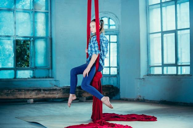 Gymnaste gracieuse effectuant un exercice aérien au loft