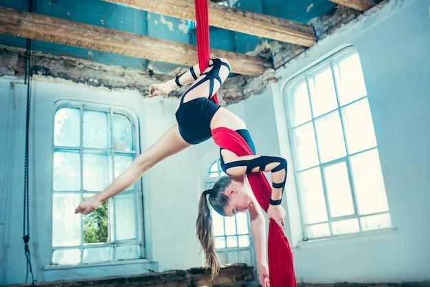 Gymnaste gracieuse effectuant des exercices aériens avec des tissus rouges sur fond bleu vieux loft.