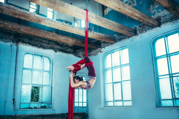 Gymnaste gracieuse effectuant des exercices aériens avec des tissus rouges sur un vieux loft bleu