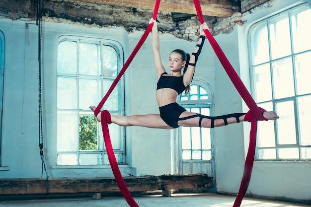Gymnaste gracieuse effectuant des exercices aériens avec des tissus rouges