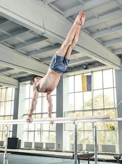 Gymnaste masculin effectuant le poirier sur des barres parallèles