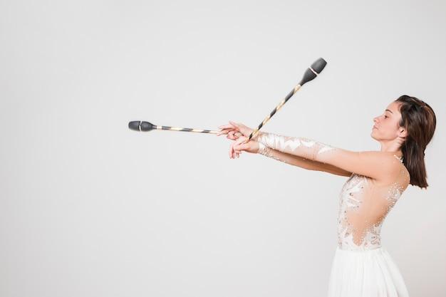 Gymnaste rythmique posant avec les clubs de jonglerie