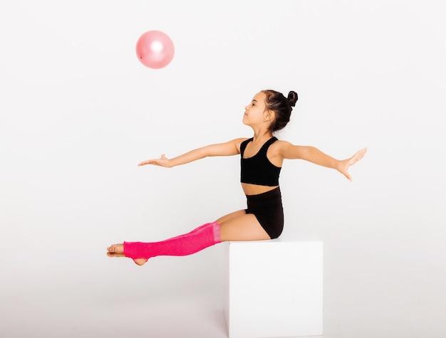 Gymnastique artistique. petite fille flexible joue avec une balle sur fond blanc.