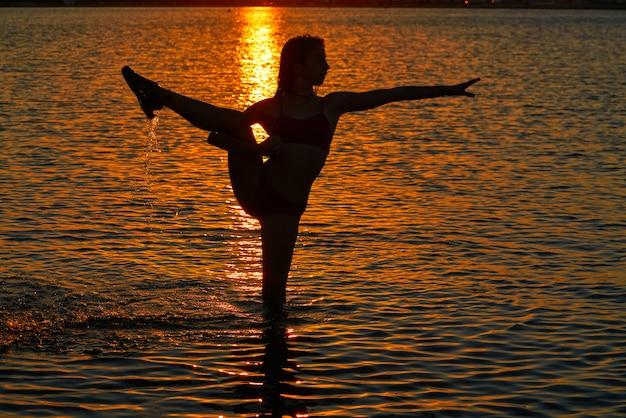 Gymnastique fille pose au coucher du soleil plage